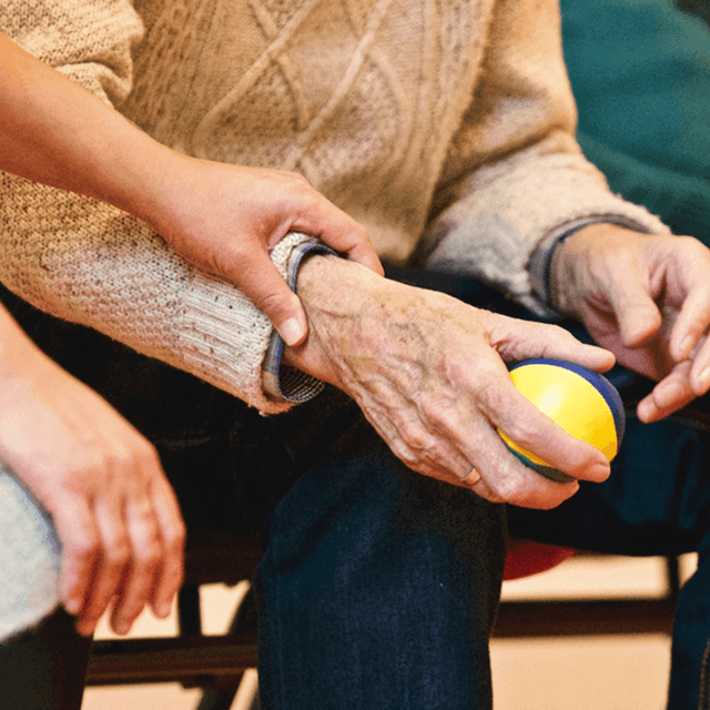 senior citizen gripping ball with assistance from nurse's hand